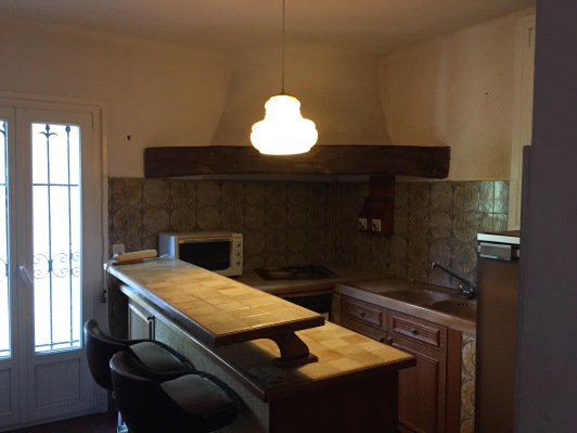 Seventies style kitchen with brown tiles and a huge corner chimney