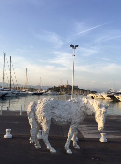 Life size sculpture of a horse in front of the marina and fort at Antibes