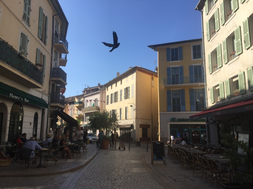 Two well-known cafes facing each other on a street in the centre of Vence