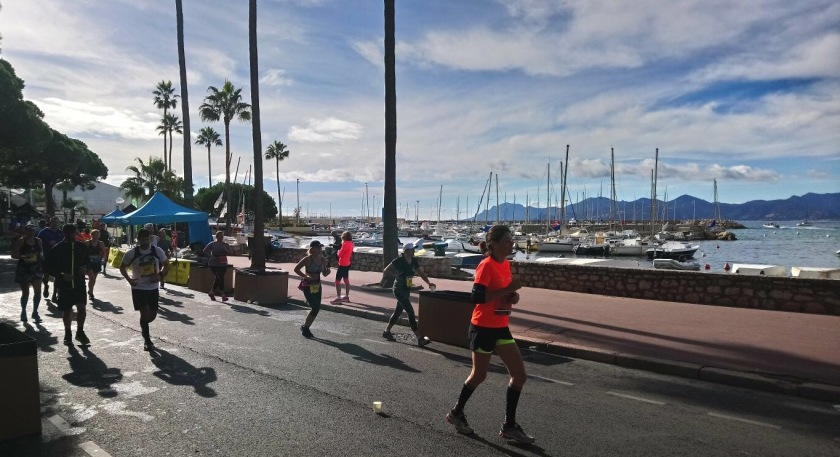 Marathon runners running along the coast coming into Cannes with a marina and mountains in the background
