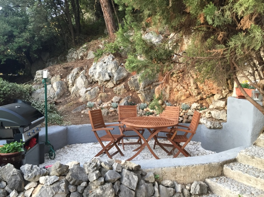 Patio with table and chairs surrounded by forest and rocks