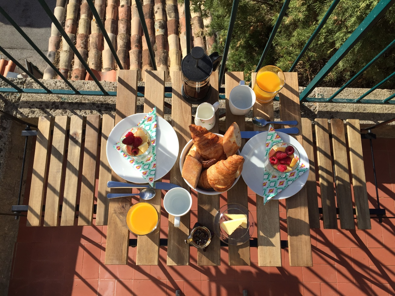 A breakfast table laid on the terrace at Villa Rocamar: fruit, yoghurt, granola and juice, croissant and baguette with coffee.